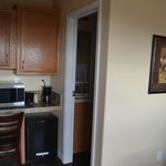 Hotel Room Image - Desk, Microwave, and Bathroom Entry