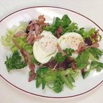 Poached Eggs On A bed Of Mixed Leaves Topped With Crispy Bacon Strips