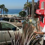 An artist painting the scene of Manhattan Beach pier from a high vantage point. Los Angeles.