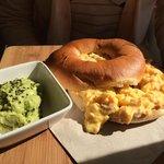 Bagel con huevos revueltos y guacamole con queso feta