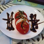 Tomato and mozzarella salad with balsamic reduction plus pine nuts.