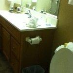 Bathroom w/ moving flooring, splatters on door, peeling finish on vanity...