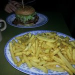 A large portion of fries with the Bacon Guacamole burger in the background.