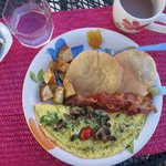 Omelet, fried potatoes, bacon, and arepas