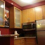 Full kitchen including dishwasher, two-burner stove, and utensils
