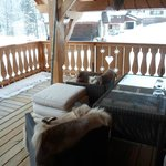 The balcony area outside the dining area with comfy chairs with fur blankets.