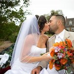 Wedding couple on carriage in front of house