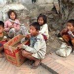 Crianças esperando os restos das ofertas