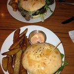 """Huge tasty burgers with """"patatas bravas"""" at top and English chips on bottom"""
