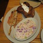 Grilled shrimp skewers, loaded baked potato and cole slaw