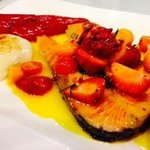 Salmon served with citrus sauce garnished with strawberries, cherry tomatoes,kumquat, onion and
