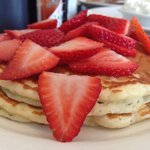 Fluffy buttermilk pancakes topped with strawberries.