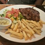 Steak with chips and garnish.