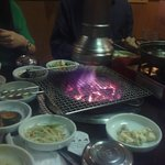 Charcoal grill in center of table, side dishes surrounding it.
