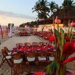 group dinner setup on the beach with dance floor