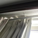 Detail of curtain rod falling loose from ceiling