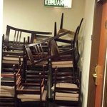 Chairs stacked in passageway obstructing emergency exit