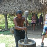 Eladio demonstrating rice husking by hand ...