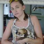 Die Volontärin, ein süßes Faultier-Baby präsentierend
