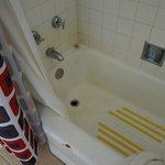 A tired, yellowed tub with a shower head barely 5 feet above