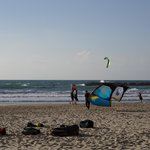 Beach full of activity, surfers and parasailers.