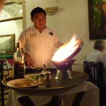 the waiter/cook flaming the food in front of us
