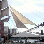 Some folks balance on a yardarm or bowsprit of the tall ship.