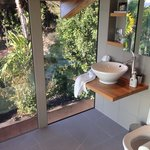 The bathroom looks out over private, lush gardens
