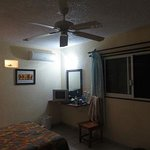 In the corner, writing desk with a light. Air conditioner above.