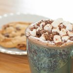 Decedent hot chocolate with all the trimmings and homemade chocolate chip cookie.