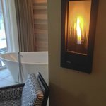 Wall mounted gas fireplace and soaker tub in front of window