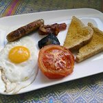 English cooked breakfast with egg, sausage, bacon, mushroom, tomato and toast.