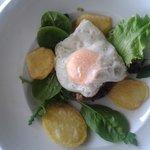 Huevos rotos con galera, morcilla y brotes frescos
