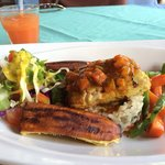 Fish of the day mahi mahi amazing! On top of rice and lentils. With roasted plantains and veggie
