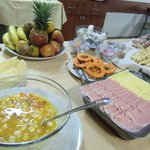mesa  de  desayuno:frutas,  ensalada  de  frutas,jamon  y  queso,  dulces  en   frasquitos.