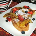 French Toast with fried banana, berries and maple syrup