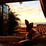 Laying on the bed, watching the sunset over the ocean.