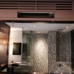 Glass walled bathroom enables guests to watch tv as they shower.