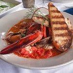 Our signature seafood stew in a savory broth with grilled half lobster