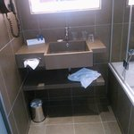 Lavabo petit, baignoire et douche bien équipées