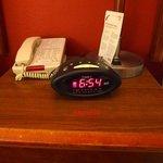 between bed table, phone, clock, lamp