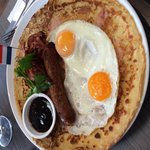 Savoury breakfast pancake with ham, bacon, sausage, egg and BBQ sauce