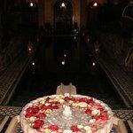 The mosiac pool lit by lanterns.