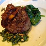 Eight-ounce Black Angus tenderloin with rustic pesto, tomato-bacon jam, and steamed spinach