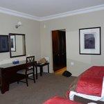La chambre comprend un bureau et un refrigérateur.