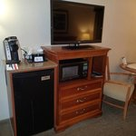View of microwave, flat screen TV, refrigerator and Keurig coffee machine