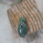 Slowly, the rough piece of greenstone transforms into a pendant.