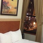 Room 222 has two double beds partial brick wall with Faux Fireplace two Windows overlooking Stre