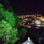 Vista noturna da cidade na área do restaurante e piscina.