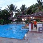 Piscina com bar estilo hotéis do Caribe. Final do dia.